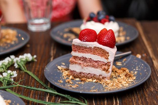 木製のテーブルの夏の果実と甘いケーキ