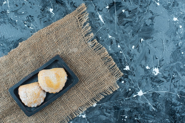 Torte dolci sul piatto di legno su una trama, sul tavolo blu.