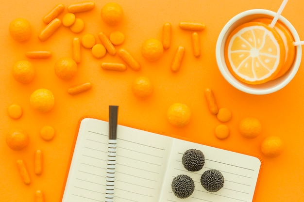 Sweet candies and lollipops with notepad and pen on orange background