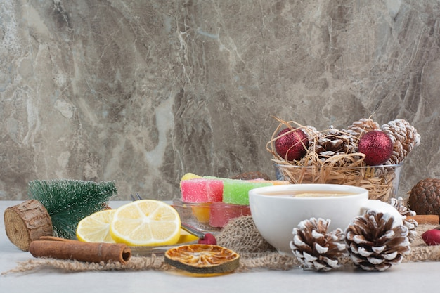 Sweet candies wih tasty cup of tea on sackcloth. high quality photo