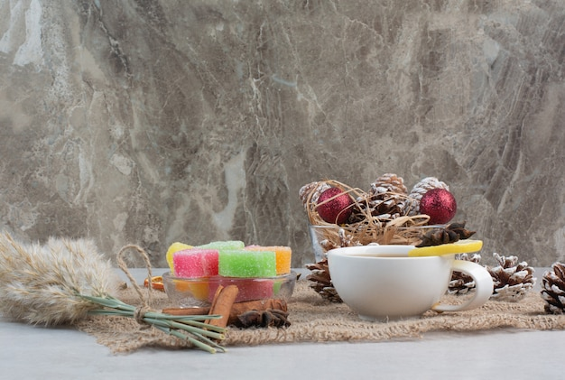 Sweet candies with tasty cup of tea on sackcloth. high quality photo