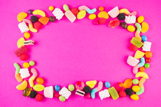 Sweet candies with various shapes forming frame on pink surface