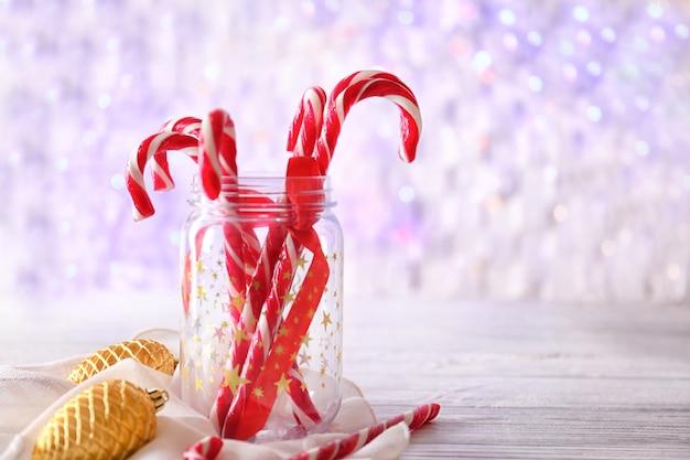 ぼやけた背景にクリスマスのおもちゃとガラスの瓶に甘いキャンディの杖