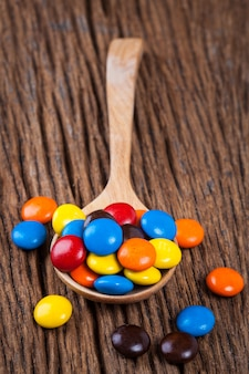 Sweet candy chocolate in spoon on wood table