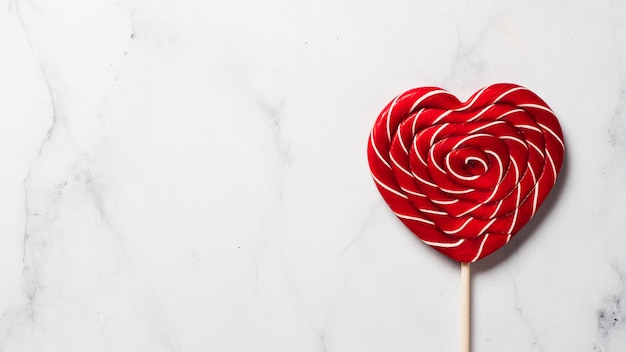 Sweet candy heart on white marble background. copy space left. top view or flat lay. banner