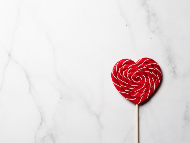 Sweet candy heart on white marble background. copy space left.