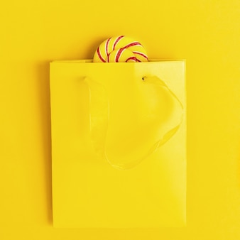 Sweet candy lollypop bright colored peeps out of yellow paper bag