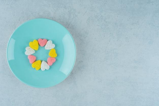白い表面の青いプレートに甘いキャンディーバレンタインハート