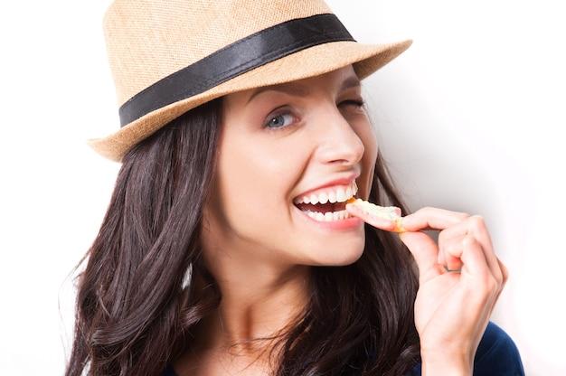 달콤한 사탕. 흰색 배경에 서 있는 동안 사탕을 먹고 펑키 모자에 젊은 아름 다운 여자