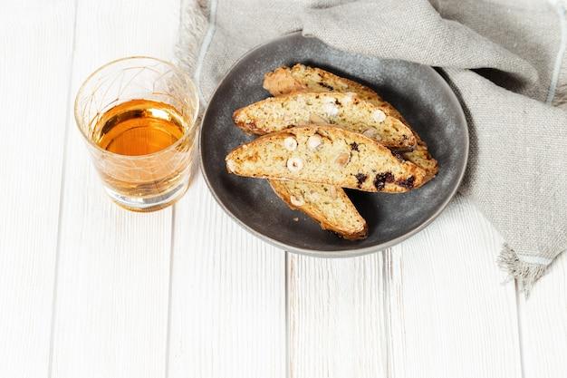 달콤한 cantuccini 비스킷과 와인. woden 테이블에 만든 이탈리아 비스코 쿠키입니다.