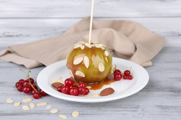Сладкое карамельное яблоко на палочке с ягодами на деревянном столе