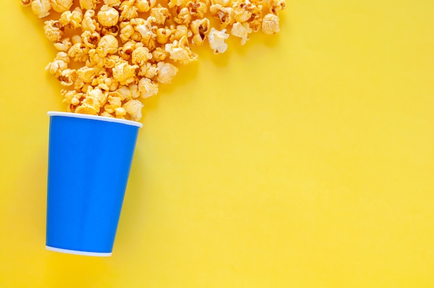 Sweet caramel popcorn in blue paper bucket.
