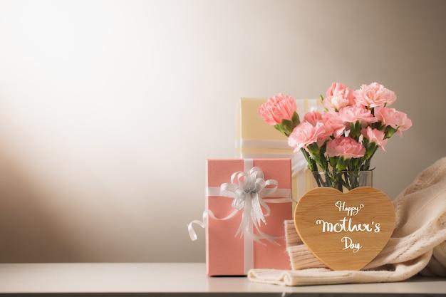 甘いカーネーションの花とテーブルの上の贈り物