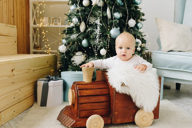 Sweet caucasian baby sitting in a wooden toy train near decorated christmas tree
