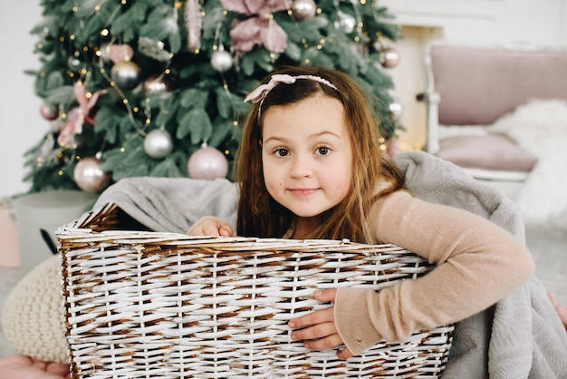 Sweet caucasian schoolgirl sitting in a basket near decorated christmas tree