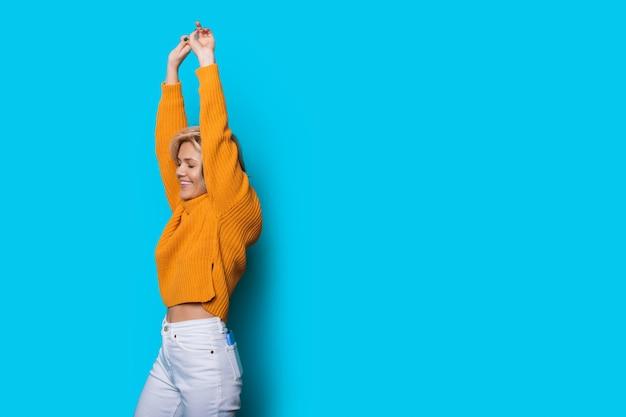 空白のスペースで青い背景に手を上げてポーズをとって甘い白人女性