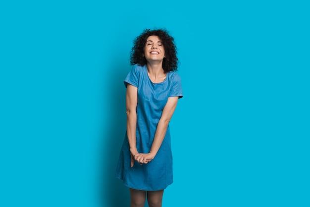 곱슬 머리를 가진 달콤한 백인 여자는 여유 공간이있는 파란색 벽에 닫힌 눈으로 포즈를 취하고 있습니다.