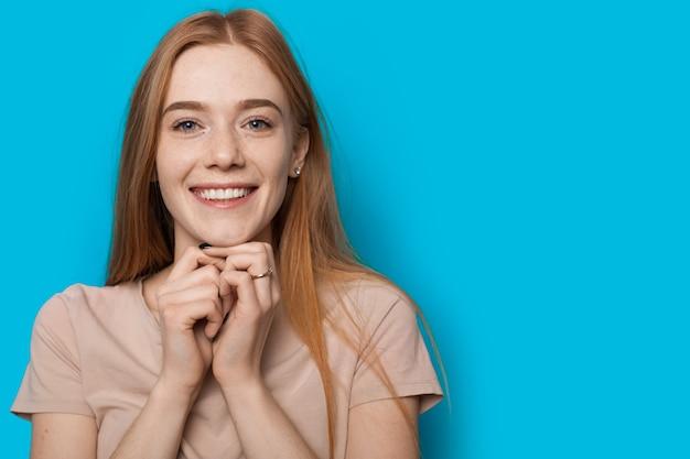 自由空間と青い壁の上のカメラに微笑んで赤い髪とそばかすを持つ甘い白人女性