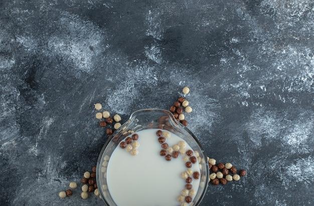 大理石の甘いシリアルボールとミルクのボウル。