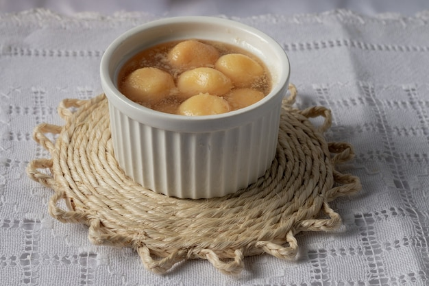 Сладкий сырный шарик в сиропе в белой фарфоровой миске