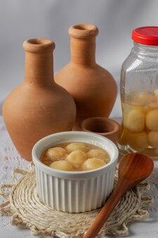 Сладкий сырный шарик в сиропе с двумя глиняными горшочками и ситечком