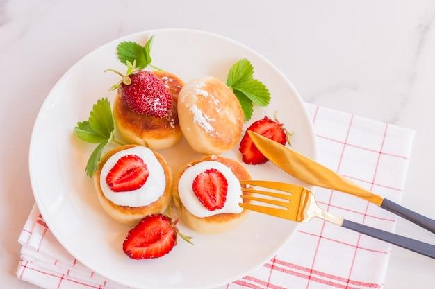 접시에 달콤한 치즈 팬케이크는 딸기와 함께 제공됩니다. 코티지 치즈 팬케이크, 시르니키, 리코타 튀김, 두부 튀김. 평면도 또는 평면도.