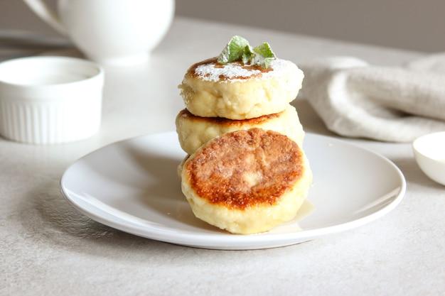 Сладкие сырники с медом и сливками на белой тарелке домашний рецепт сырников