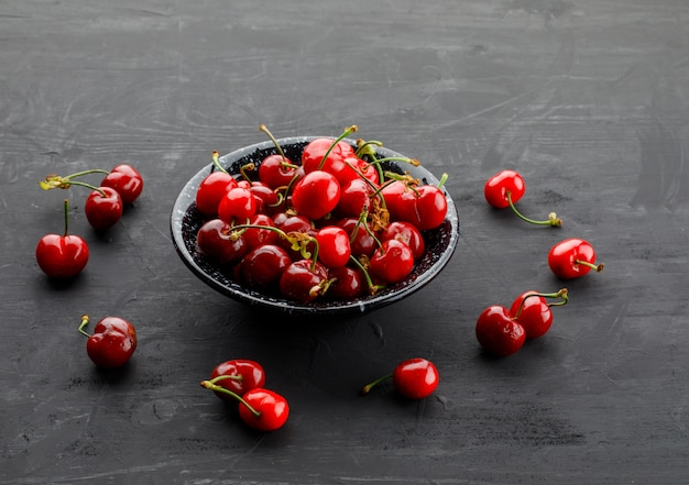 Sweet cherries in a black plate high angle view on a grey table