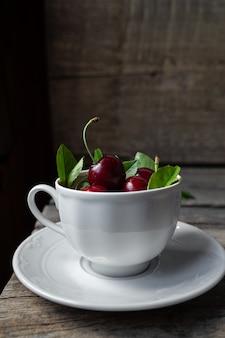 Черешня в чашке белого чая на деревянном деревенском фоне