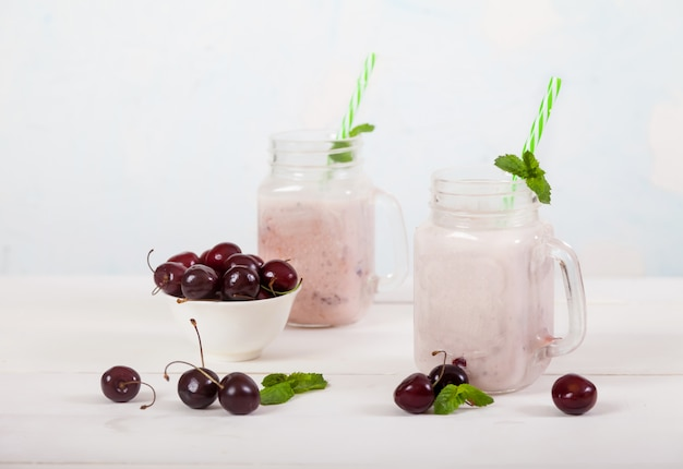 Sweet cherries and milk smoothies in two glass jars with a straw and sweet cherries in a cup