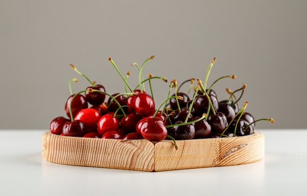 Sweet cherries in a wooden plate on white and grey surface, side view.