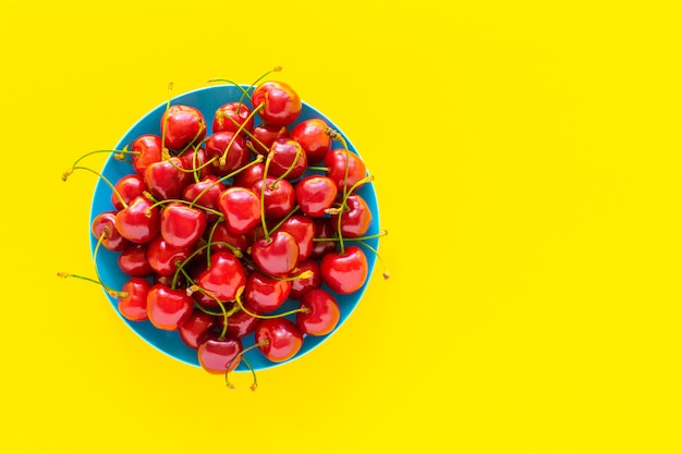 Sweet cherry in a blue plate on a yellow background.