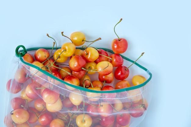 環境に優しいパッケージの甘いチェリー。野菜や果物の再利用可能なバッグ。店での買い物、小売。環境にやさしい包装。