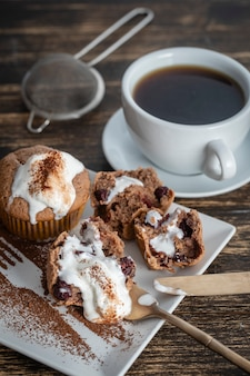 Sweet cherry muffin with ice cream and white cup with tea on a wooden background