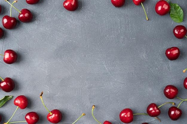 회색 배경에 달콤한 체리 잘 익은 체리 위에서 체리 레드 보기 과일 배경 잎이 있는 잘 익은 체리 프레임 상위 뷰