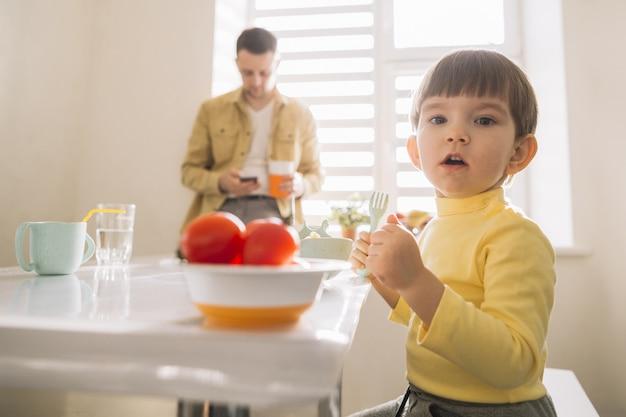 Сладкий ребенок, одетый в желтое и его отец