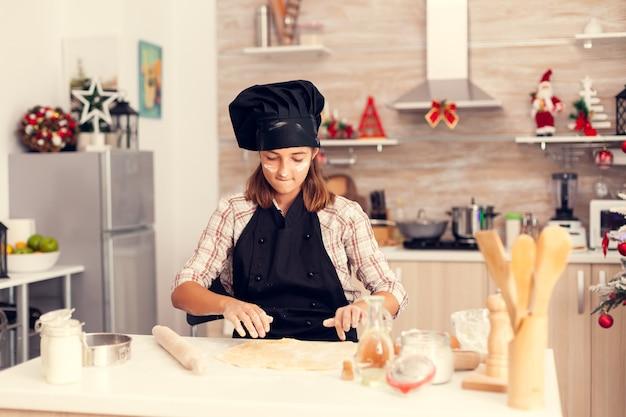 エプロンを着てクリスマスの日にデザートを作る甘い子供