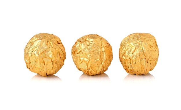 Sweet chocolate candy wrapped in golden foil isolated on white background