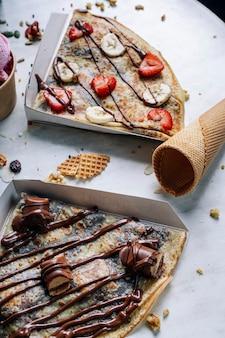 テーブルの上の甘いチョコレートクレープ。縦の写真