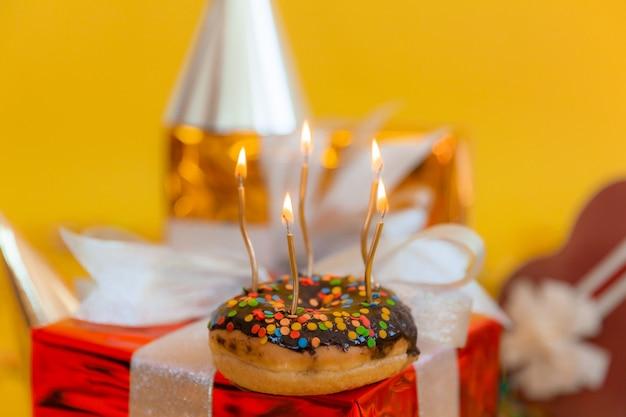 お祝いのボケ味の背景に甘いチョコレートドーナツと燃えるキャンドル。お誕生日おめでとうのコンセプト。
