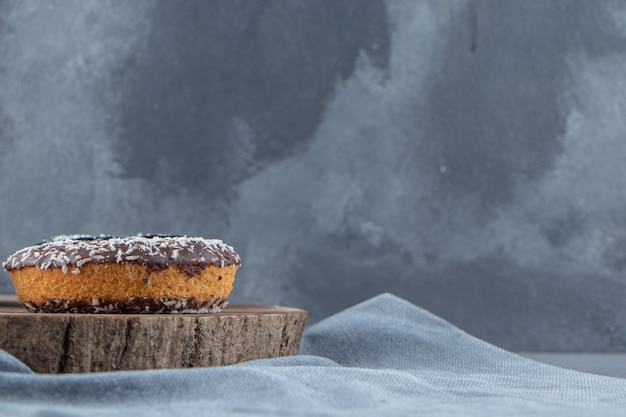 돌 배경에 나무 조각에 달콤한 초콜릿 도넛. 고품질 사진