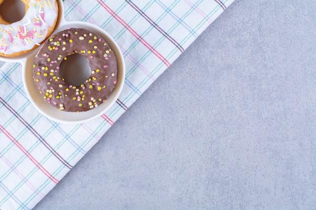 テーブルクロスにカラフルなふりかけの甘いチョコレートドーナツ。