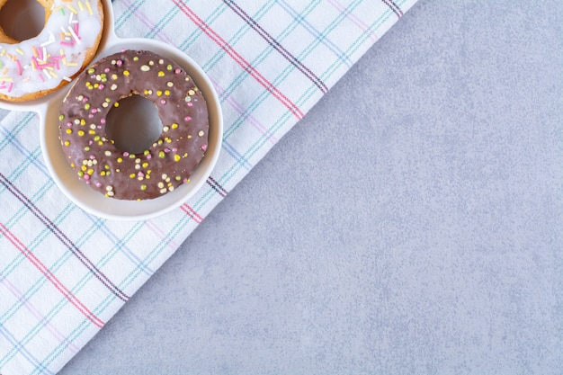 Sweet chocolate doughnuts with colorful sprinkles on a tablecloth.