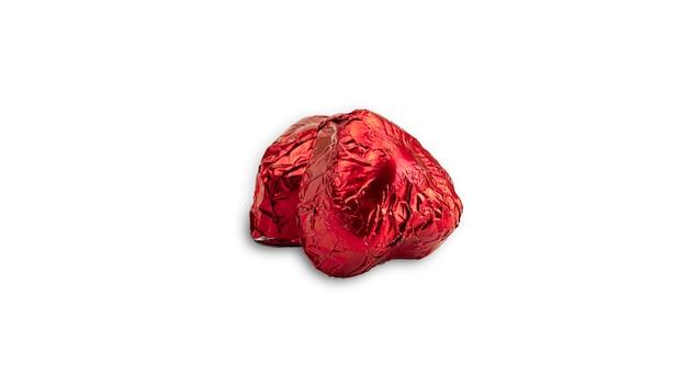 赤いホイルに包まれた甘いチョコレートのハート型キャンディ