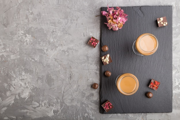 Sweet chocolate liqueur in glass and black stone slate board. top view