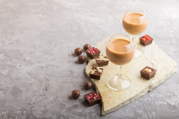 Sweet chocolate liqueur in glass and stone slate board. side view