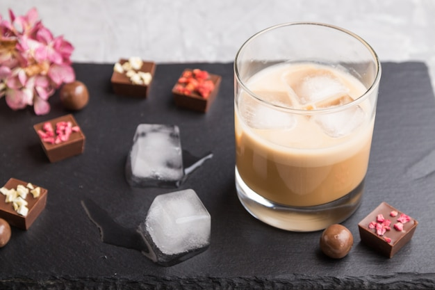 コンクリートの灰色の背景と黒い石のスレート板のガラスに氷と甘いチョコレートリキュール。側面図、セレクティブフォーカス。