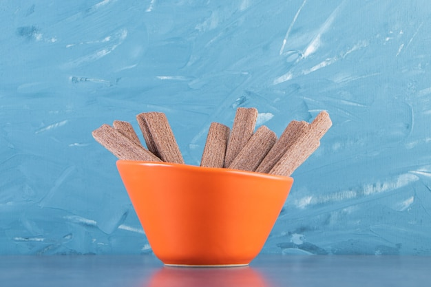Sweet chocolate wafer roll in a bowl, on the marble background.