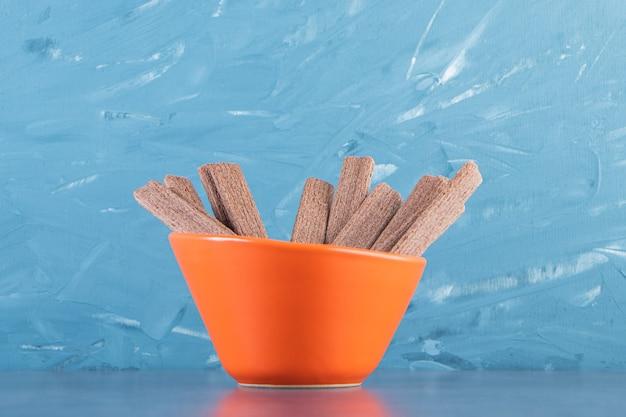 Сладкий шоколадный вафельный рулет в миске, на мраморном фоне.