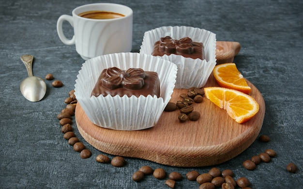 Sweet chocolate waffle cakes on a wooden board and a cup of coffee, dessert, treats